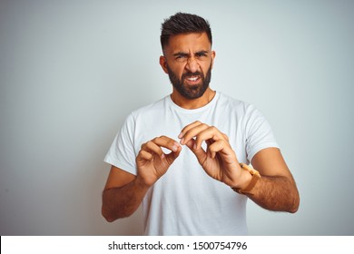 Young indian man wearing t-shirt standing over isolated white background disgusted expression, displeased and fearful doing disgust face because aversion reaction. With hands raised. Annoying concept.