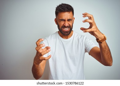 Young indian man wearing t-shirt standing over isolated white background Shouting frustrated with rage, hands trying to strangle, yelling mad