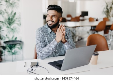 Young indian man working on laptop in modern office