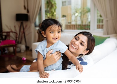 Young Indian mother and her little daughter having fun at home