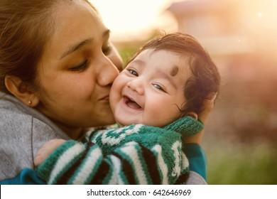 Young Indian mother kissing her beloved baby