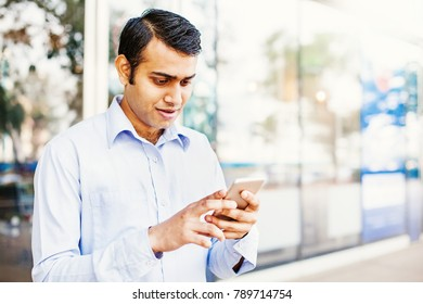 Young indian office worker looking at his phone with shock