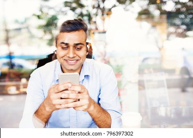 Young indian office worker using his phone in a cafe
