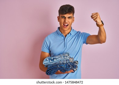 Young indian shopkeeper man holding folded jeans standing over isolated pink background annoyed and frustrated shouting with anger, crazy and yelling with raised hand, anger concept