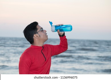 Young Indian sportsman drinking water at beach