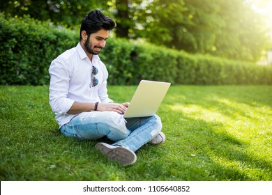 Young indian Student with a laptop sitting on the grass. Urban style.