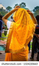 Young Indian woman adjusts her sari scarf on her head