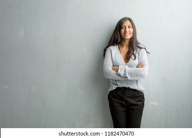 Young indian woman against a grunge wall crossing his arms, smiling and happy, being confident and friendly