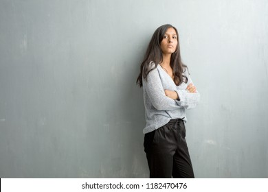 Young indian woman against a grunge wall crossing his arms, serious and imposing, feeling confident and showing power