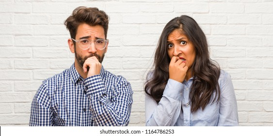 Young indian woman and caucasian man couple biting nails, nervous and very anxious and scared for the future, feels panic and stress