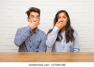 Young indian woman and caucasian man couple covering mouth, symbol of silence and repression, trying not to say anything