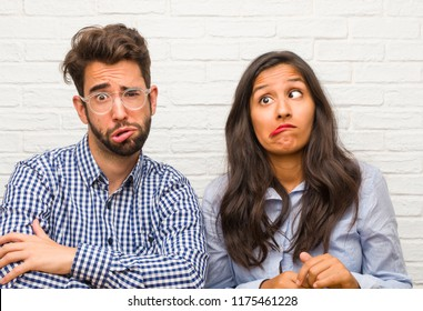 Young indian woman and caucasian man couple crazy and desperate, screaming out of control, funny lunatic expressing freedom and wild
