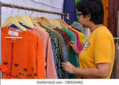 A young Indian woman checking designer kurta ( Salwar Kamiz) on display at a shop in Dilli Haat, New Delhi, India