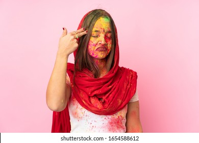 Young Indian woman with colorful holi powders on her face isolated on pink background with problems making suicide gesture