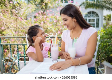 Young Indian woman and daughter talking and drinking cocktails