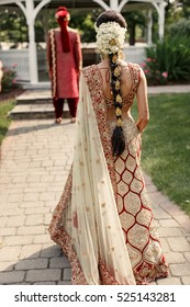 Young Indian woman dressed in golden wedding suit walks to a grooms standing in the garden