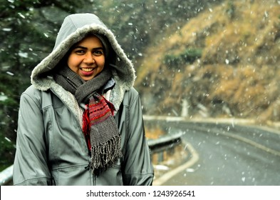 Young Indian woman enjoying her first snowfall during winter holidays in Kufri, Shimla, Himachal Pradesh. It is a popular winter getaway where people come to enjoy snowfall, skiing and winter sports