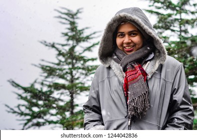 Young Indian woman enjoying her first snowfall during winter holidays in Kufri, Shimla, Himachal Pradesh. It is a popular winter getaway where people come to enjoy snowfall, skiing and winter sports.