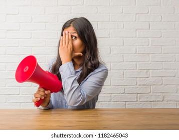 Young indian woman feels worried and scared, looking and covering face, concept of fear and anxiety. Holding a megaphone.