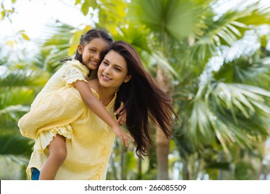 Young Indian woman giving piggyback ride to her daughter