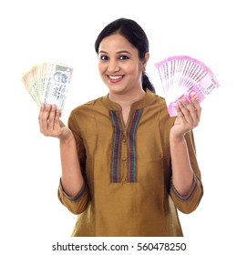 Young Indian woman holding currency notes against white background