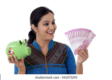 Young Indian Woman holding a Piggy bank and Indian rupee notes-Money saving concept