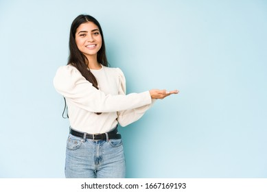 Young indian woman isolated on blue background holding a copy space on a palm.