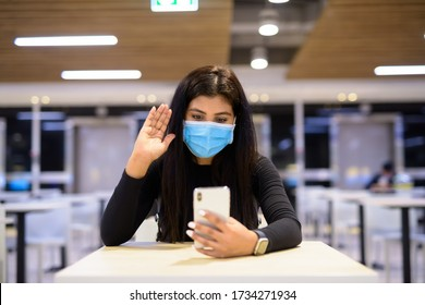 Young Indian woman with mask video calling using phone and sitting with distance at food court