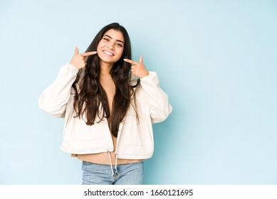 Young indian woman on blue background smiles, pointing fingers at mouth.