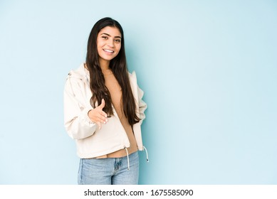 Young indian woman on blue background stretching hand at camera in greeting gesture.