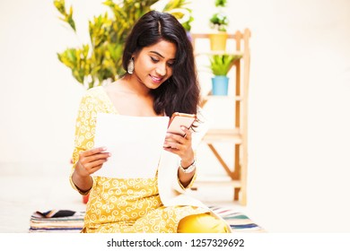 Young indian woman paying bills with mobile phone