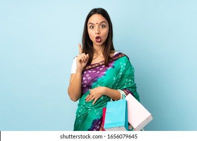 Young Indian woman with shopping bags intending to realizes the solution while lifting a finger up