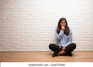 Young indian woman sit against a brick wall biting nails, nervous and very anxious and scared for the future, feels panic and stress