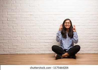 Young indian woman sit against a brick wall crossing his fingers, wishes to be lucky for future projects, excited but worried, nervous expression closing eyes
