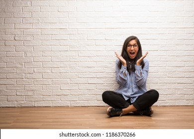 Young indian woman sit against a brick wall surprised and shocked, looking with wide eyes, excited by an offer or by a new job, win concept