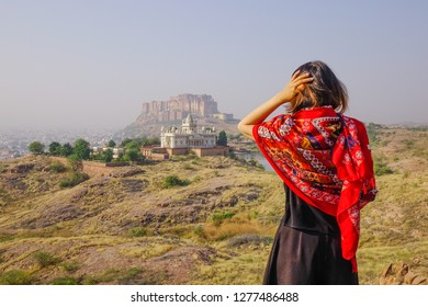 Young Indian woman standing on the hill and looking at the white temple in Jodhpur, India.