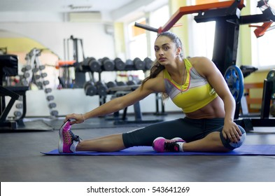 Young Indian woman stretches at the gym