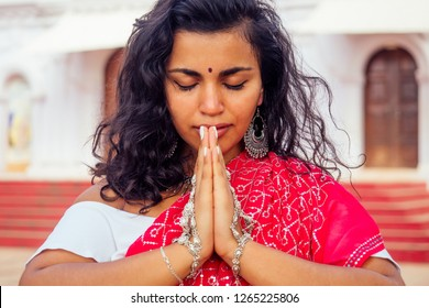 Young Indian woman in traditional sari red dress praying in a hindu temple goa india Hinduism.girl performing namaste gesture catholicism Delhi Street holi festival.om yoga meditation female model