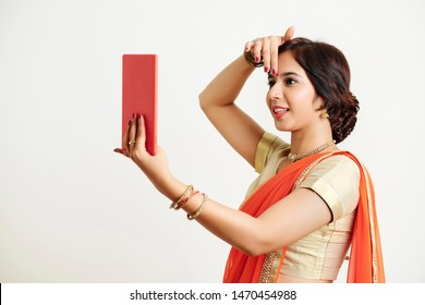 Young Indian woman using selfie camera on tablet computer when applying bindi between eyebrows