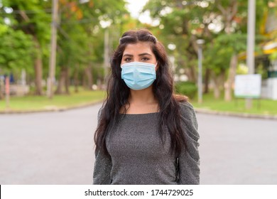 Young Indian woman wearing mask for protection from corona virus outbreak at the park outdoors