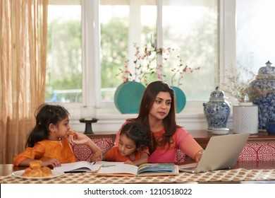 Young Indian woman working on laptop when two children playing and reading books next to her