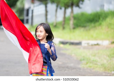 Young Indonesian Girl Holds Her Red-White Flag