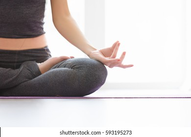 Young indonesian woman meditating, doing yoga lotus pose and asana. Fitness girl enjoying yoga indoors in sport clothes, working out in gym class close up, copyspace