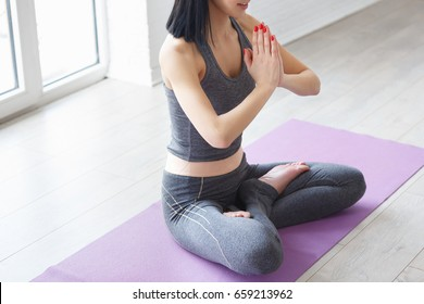 Young indonesian woman meditating, doing yoga lotus pose and asana. Fitness girl enjoying yoga indoors in sport clothes, working out in gym class