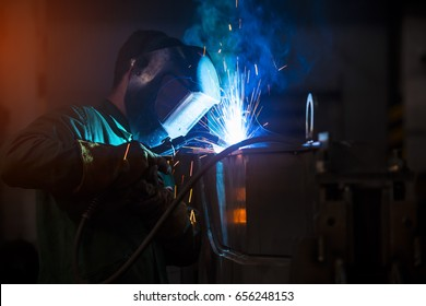 Young industrial worker welding in the factory
