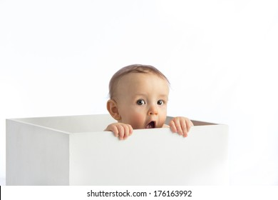 A young infant boy peeking out of a box on a white background