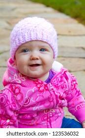 A young infant girl wearing a pink sweatshirt and a knitted cap sits on a stone walkway for a portrait.