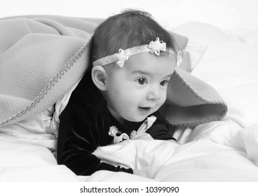 A young infant looking out from under a blanket.