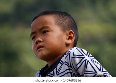 A young inhabitant of a village near the rice fields of Yunnan, China. The famous terraced rice fields of Yuanyang in Yunnan province in China. Yunnan, China - November, 2018