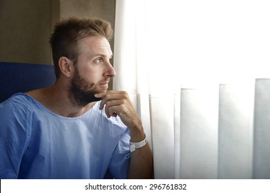 young injured man in hospital room sitting alone in pain looking on window negative and worried for his bad health condition sitting on chair suffering depression on sad lonely background